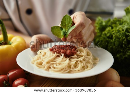 Woman chef hands decorating pasta with bolognese sauce. Tasty meal preparation concept. - stock photo