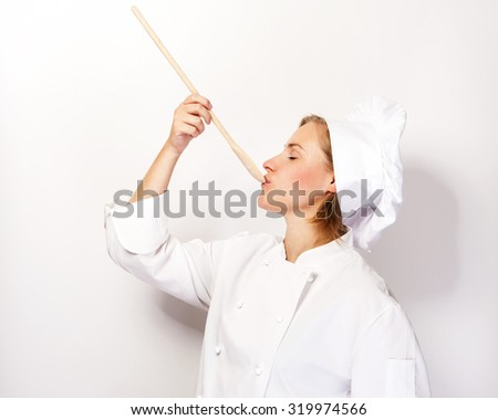 Woman chef holding a spoon and tasting from spoon. On white background. - stock photo