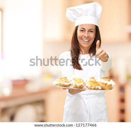 Woman chef holding baked food, indoor