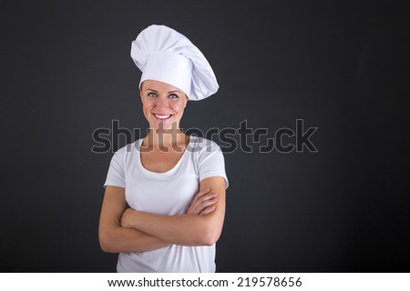 woman chef smiling over dark background - stock photo