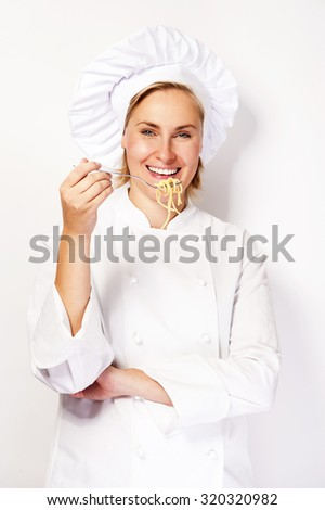 Woman chef with fork and spaghetti, pasta noodles, smiling over white background. - stock photo