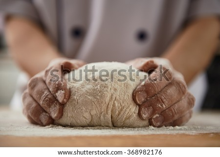 Woman chef with raw dough. Young female in uniform preparing bread dough on wooden table.  - stock photo