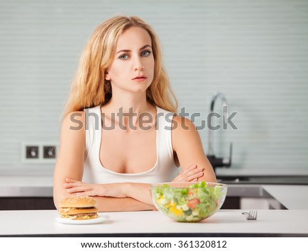 Woman chooses between a healthy and unhealthy food - stock photo