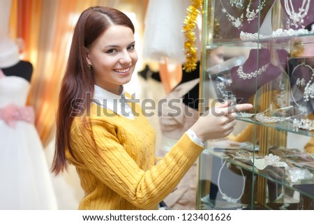 woman chooses bridal accessories in wedding boutique - stock photo