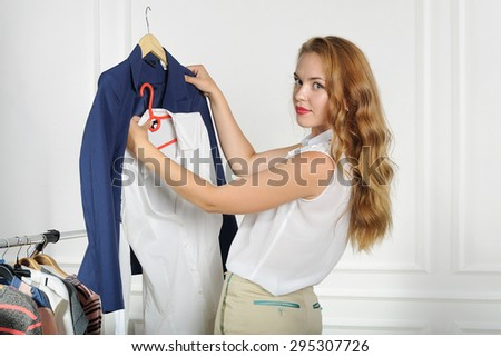 Woman chooses clothes in a clothing store comparing things with each other against the light background - stock photo