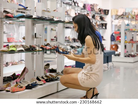 woman chooses shoes in shop - stock photo