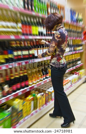 Woman chooses wine in a supermarket. - stock photo