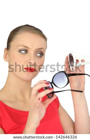 Woman choosing a pair of sunglasses - stock photo