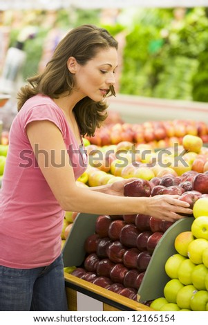 Woman choosing apples in produce department of supermarket - stock photo