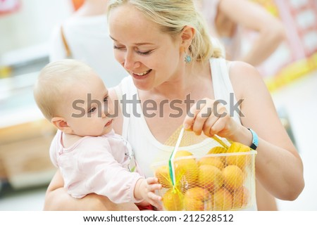 woman choosing apricot with child during shopping at fruit vegetable supermarket - stock photo
