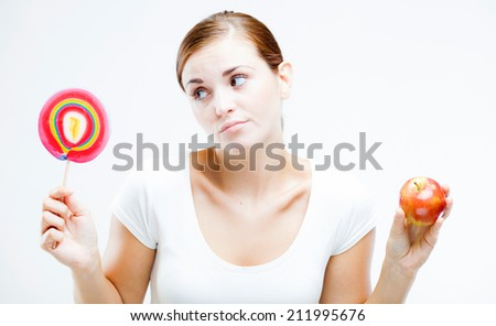Woman choosing between sweets and fruits, healthy or unhealthy food concept - stock photo