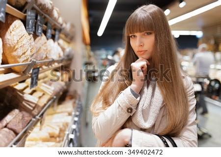 Woman choosing bread at supermarket - stock photo