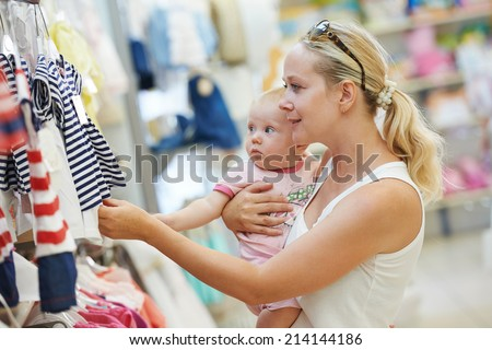 woman choosing children apparel with little baby child on hands in clothing shop supermarket - stock photo