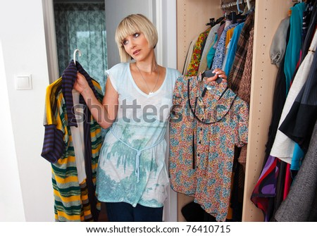 woman choosing clothes in front of full closet - stock photo