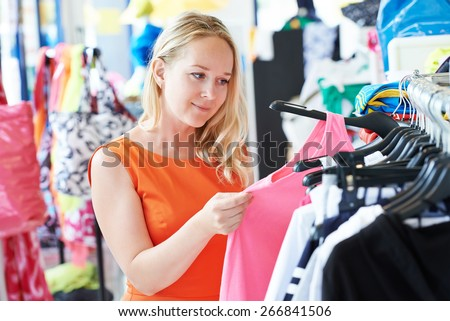 woman choosing dress during shopping at garments apparel clothing shop - stock photo