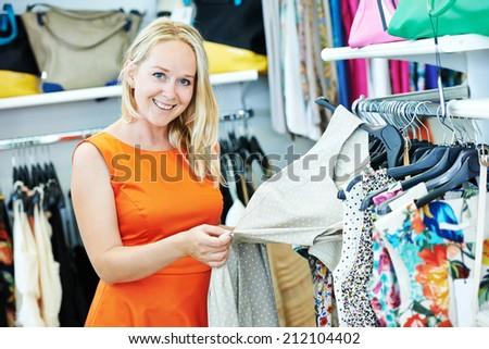 woman choosing dress during shopping at garments clothing shop - stock photo