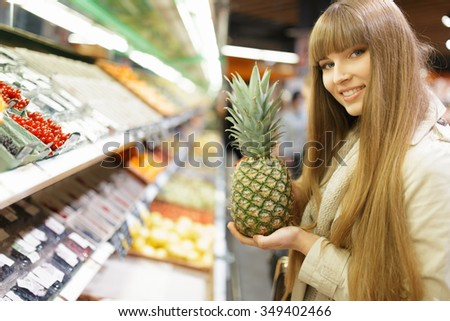 Woman choosing fruits at supermarket and holding pineapple - stock photo