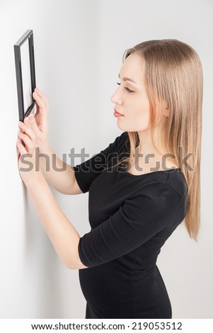 Woman choosing place for picture on the wall at home interior - stock photo