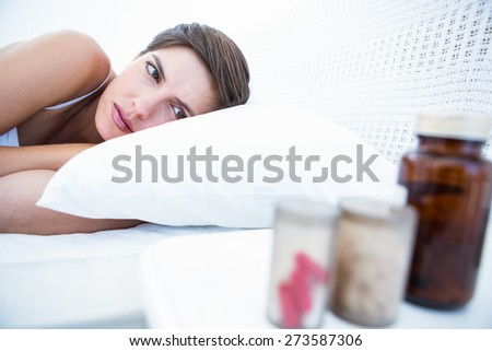 Woman choosing to take pills or not at home in the bedroom - stock photo