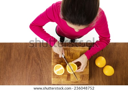 woman chopping up a orange taken from a birds eye view looking down - stock photo