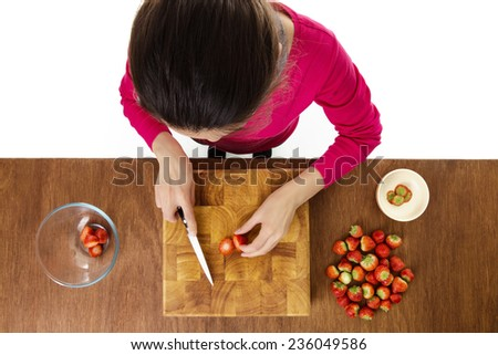 woman chopping up strawberries on a wooden chopping board taken from a birds eye view from above looking down - stock photo