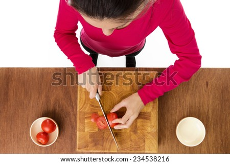 woman chopping up tomatoes on a wooden chopping board taken from a birds eye view from above - stock photo