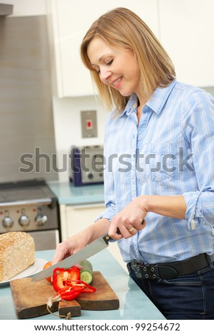 Woman chopping vegetables in domestic kitchen - stock photo