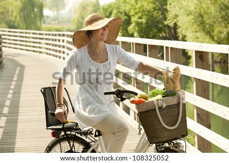 Woman cicyling with vegetables on her basket - stock photo