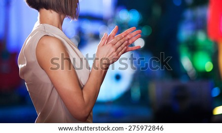 Woman clapping - stage in the background - stock photo