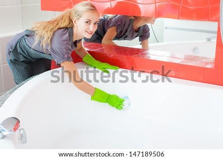 Woman cleaning bath at home. Female washing bathtub. Tub - stock photo