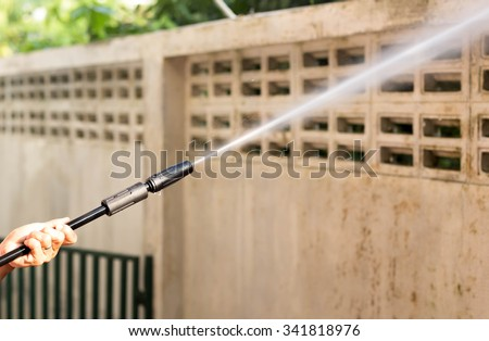 woman cleaning dirty waill with high pressure water jet - stock photo