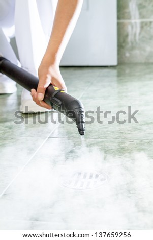 Woman cleaning  drain in bathroom with a lot of steam - stock photo