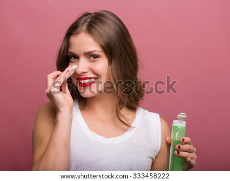 Woman cleaning her face with a lotion and a cotton pad - stock photo