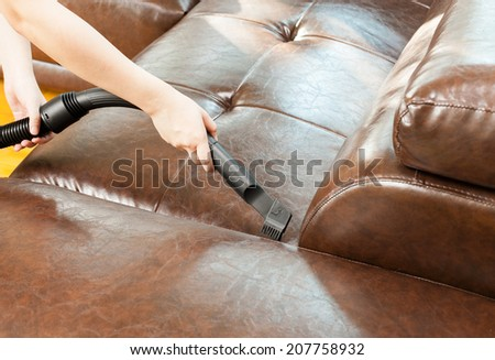 woman cleaning leather sofa with vacuum cleaner  - stock photo
