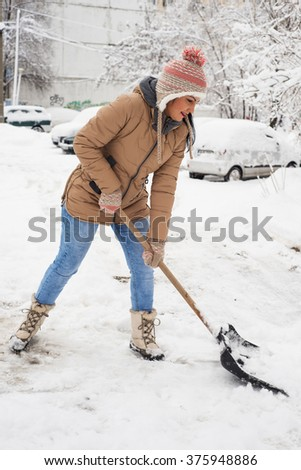 Woman  cleaning snow in parking  in cold day