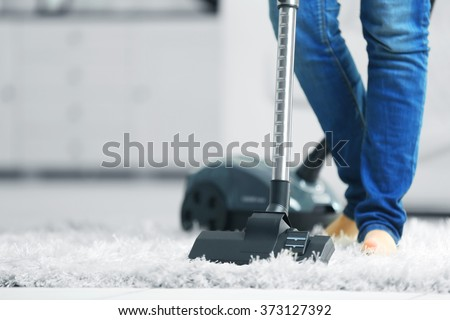 Woman cleaning the carpet with vacuum cleaner in the living room - stock photo