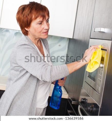Woman cleaning the kitchen. Adult woman washing microwave - stock photo