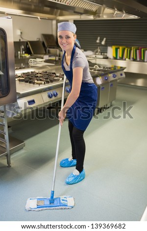 Woman cleaning the kitchen in the restaurant - stock photo