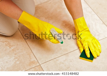 Woman cleaning tile floors by hand, wearing yellow gloves