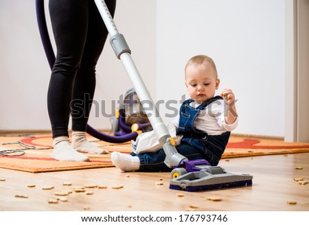 Woman cleaning with vacuum cleaner, baby sitting on floor and biscuits all around - stock photo