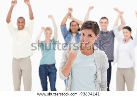 Woman clenching her fist with people behind raising their arms against white background