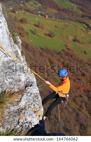 Woman climber abseiling in order to descent the route - stock photo