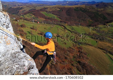 Woman climber abseiling on yellow rope, high above ground - stock photo