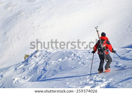 Woman climber carries skies on the backpack on crust covered slope - stock photo