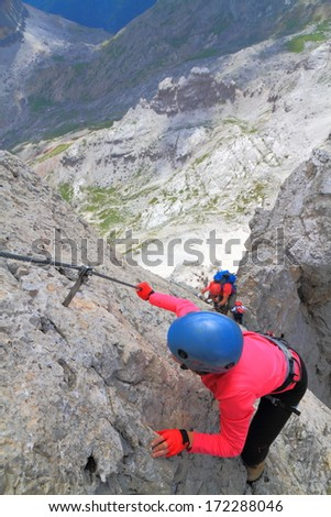 Woman climber on aerial section of via ferrata route, Dolomite Alps, Italy - stock photo