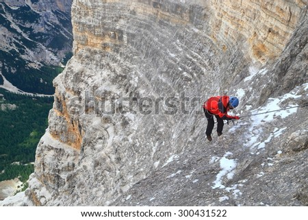 "Woman climber on steep section of via ferrata ""Lipella"", Tofana massif, Dolomite Alps, Italy - stock photo"