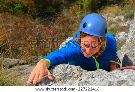Woman climber reaches for a hand hold on steep limestone route - stock photo