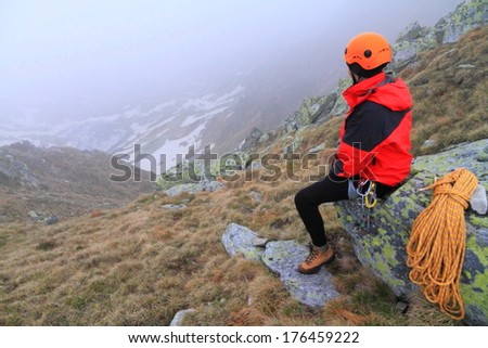 Woman climber rests on the mountain in foggy weather - stock photo