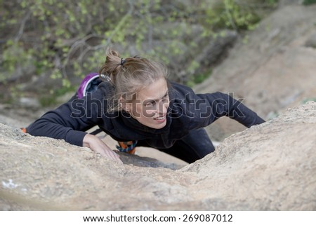 woman climbing a hard wall - stock photo