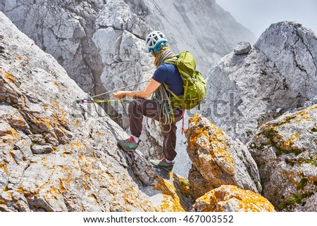 woman climbing in mountains of Austria / Extreme Sports in the Alps / Woman securing climber